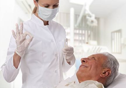 Older man in chair smiling at dentist