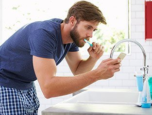 man brushing teeth while on cellphone