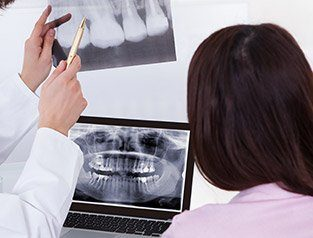 dentist pointing to x-rays