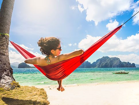 woman laying in red hammock