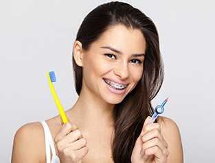 Woman holding a toothbrush and flosser.