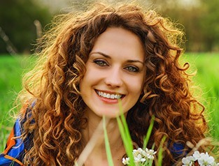 woman with curly hair smiling outside
