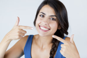 Woman pointing to smile