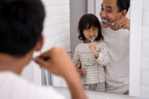 parent brushing their teeth with their child