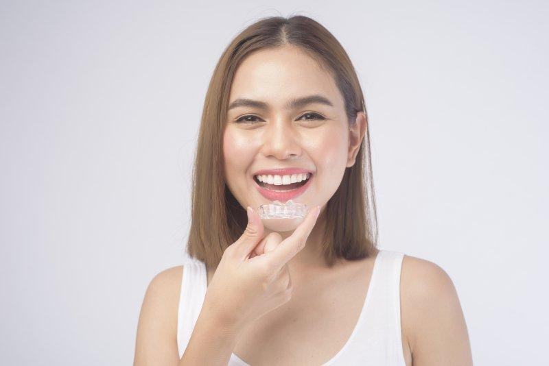 girl smiling and holding Invisalign aligner