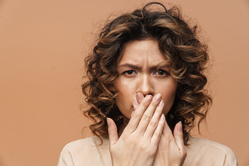 young woman frowning and covering mouth